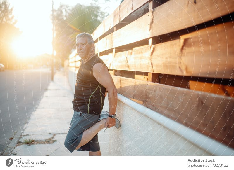 Elderly man stretching on wooden wall in street sportive elderly mature old shape training runner athlete workout fitness city healthy athletic exercise