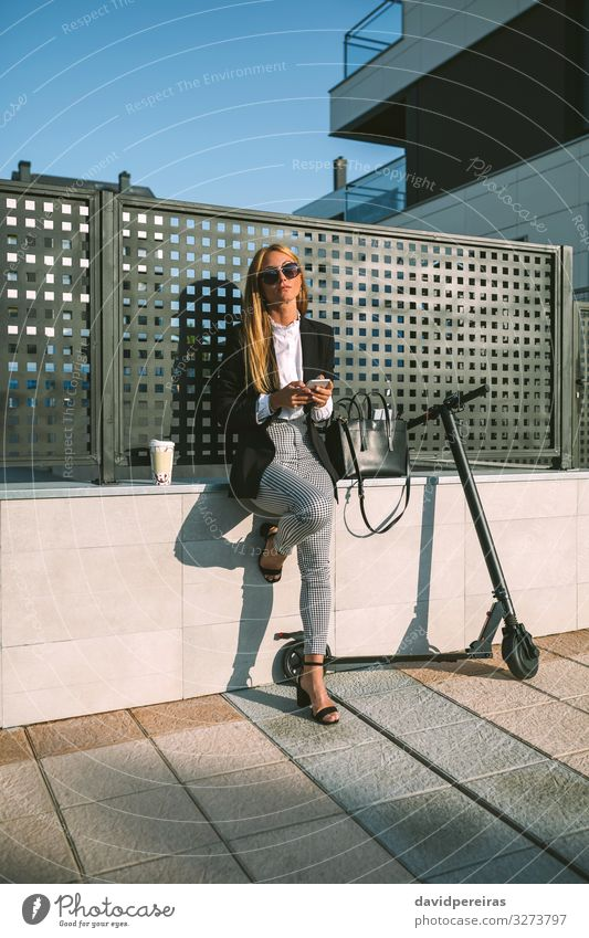 Businesswoman using mobile with her scooter next Lifestyle Style Beautiful PDA Human being Woman Adults Street Fashion Sunglasses Sit Wait Modern attractive