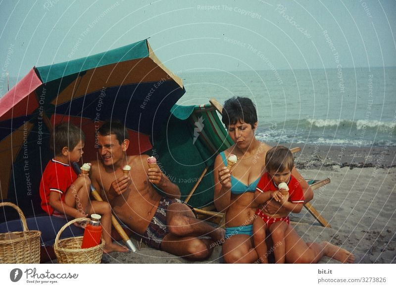 Young, happy family in swimsuits is sitting on the beach, under a parasol, having a picnic with ice cream, in Italy by the sea, back in the 60's. They hold waffle ice cream in their hands and enjoy, eat it in front of the sea.