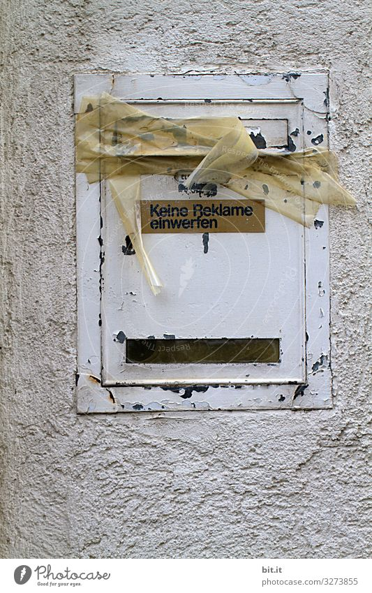 Writing on sign: Do not insert advertising, hangs on old, broken, white mailbox made of tin, on the wall of the house. The box is glued with parcel tape, tape, masking tape, closed as an indication of prohibition, tenant moving, vacancy.