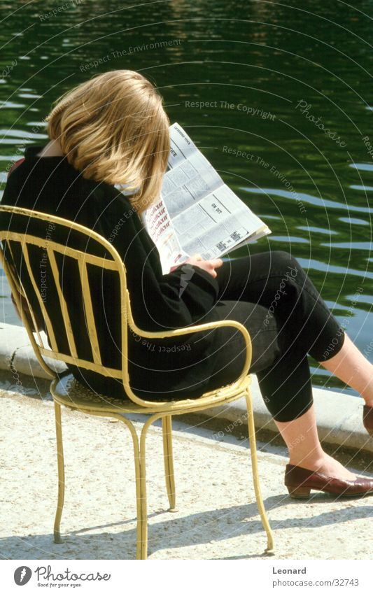 reader Woman Print media Reading Magazine Seating Pond Break Calm Newspaper Revue Human being Sun Sit Chair water young shade