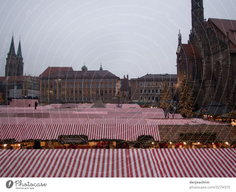 The Christmas market in Nuremberg is roofed. . The stalls are covered with red. White awnings roofed. In the background you can see half-timbered houses. Joy