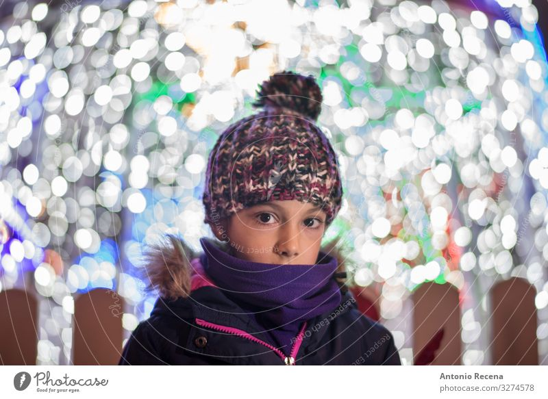 Portrait of shy girl with lights of christmas Lifestyle Joy Winter Decoration Child Infancy Warmth Coat Scarf Hat Cute holidays cold illusion lighting wool hat