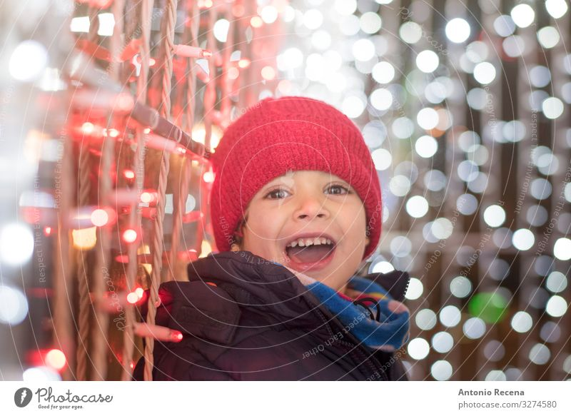 Smiling boy in christmas night looking at camera Joy Winter Feasts & Celebrations Child Human being Boy (child) Scarf Hat White Emotions Surprise holidays cold