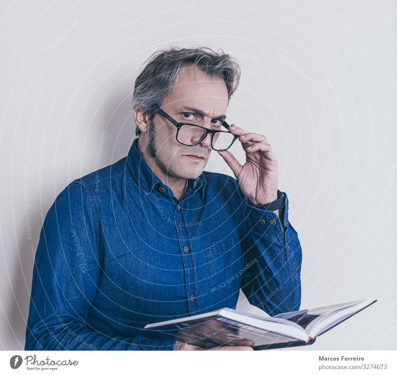 man with presbyopia reading a book Lifestyle Health care Masculine Man Adults Body 1 Human being 30 - 45 years Shirt Eyeglasses Long-haired Facial hair Book