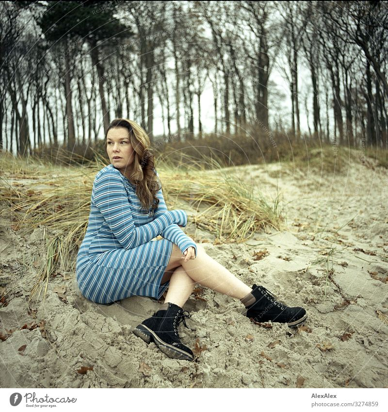 Young woman sitting on dune Style Joy Beautiful Life Youth (Young adults) Adults 18 - 30 years Landscape Flower Grass Bushes Beach Dune Dress Hiking boots