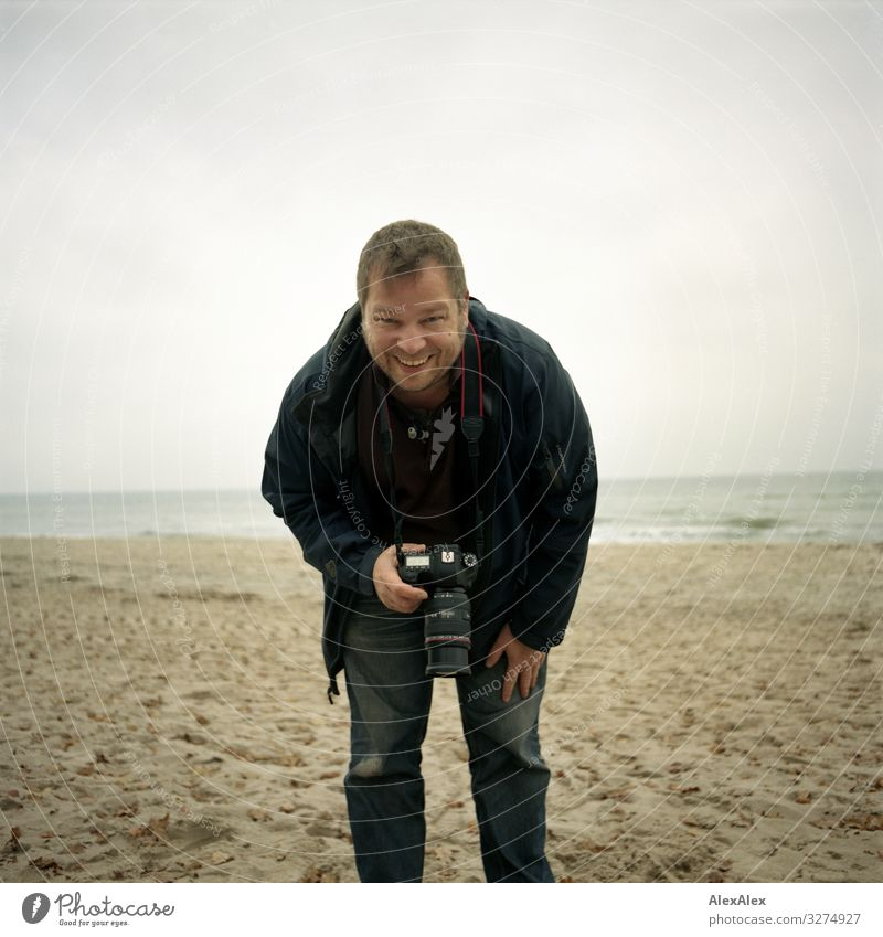 Photographer at the Baltic Sea beach Lifestyle Joy Trip Adventure Camera Man Adults 30 - 45 years Landscape Autumn Beach Jeans Jacket Blonde Short-haired Sand
