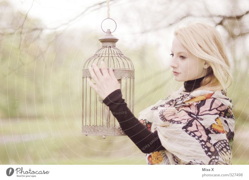 Golden cage Human being Feminine Boy (child) Woman Adults Life 1 18 - 30 years Youth (Young adults) Garden Park Blonde Pet Bird Dream Sadness Emotions Moody