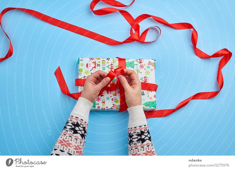 hands in a sweater knotted a red ribbon Decoration Feasts & Celebrations Christmas & Advent New Year's Eve Birthday Woman Adults Hand Fingers Paper Package