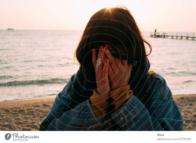 A young woman stands on the beach and hides her face in her hands. Pain, grief, anonymous. Feminine Young woman Youth (Young adults) Woman Adults 13 - 18 years