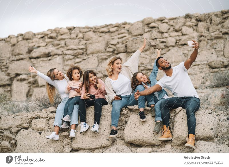 Big multiethnic family travelling together on nature selfie smile happy stone wall beige sight adventure vacation weekend children diverse black