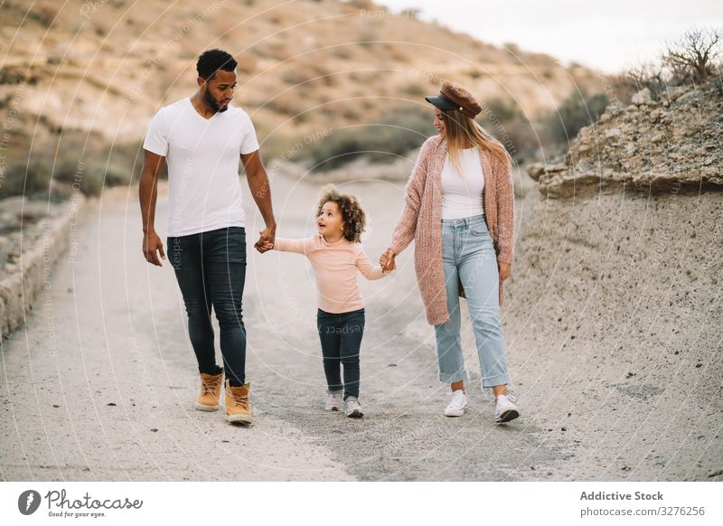 Stylish multiethnic family walking on nature hold hands together parent toddler rest smile happy stroll cheerful lifestyle modern child man bonding love tender