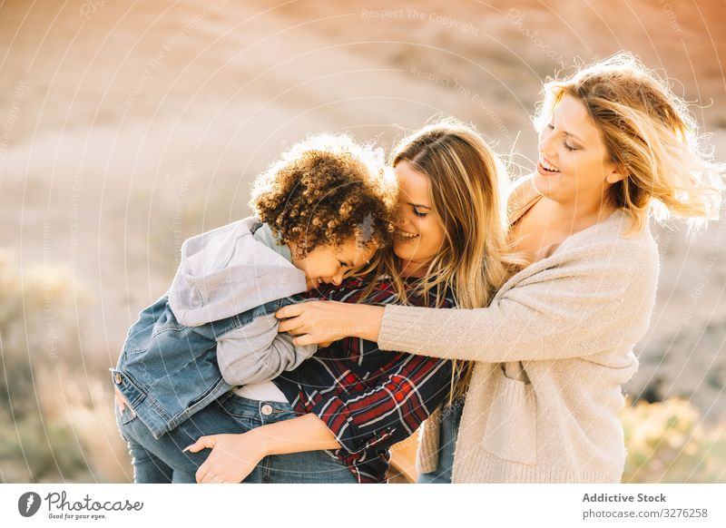 Smiling blond women walking with curly child toddler fun nature play rest smile happy cheerful lifestyle modern bonding love tender casual kid innocence joy