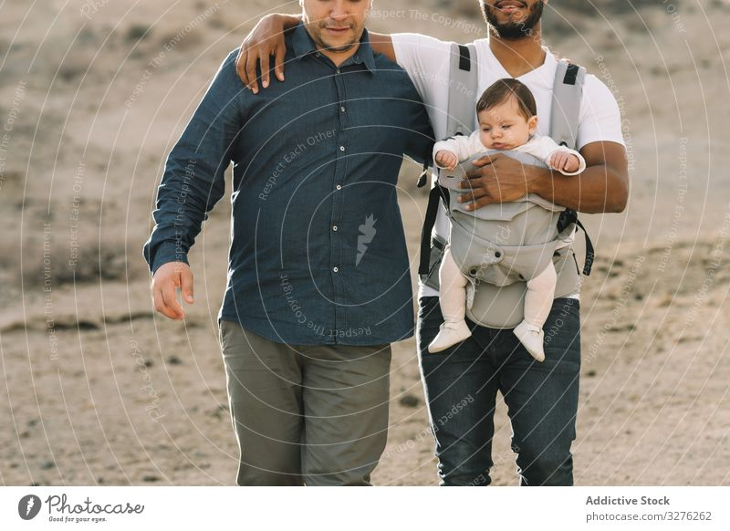 Unrecognizable diverse men walking with baby on nature gay together carrier support cuddle generation interaction lgbt homosexual stroll father male child