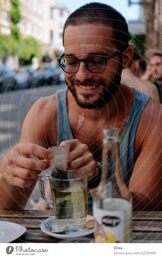 A man who sits outside in a café in the summer and drinks a tea and smiles Human being Masculine Young man Youth (Young adults) Man Adults Smiling Tea