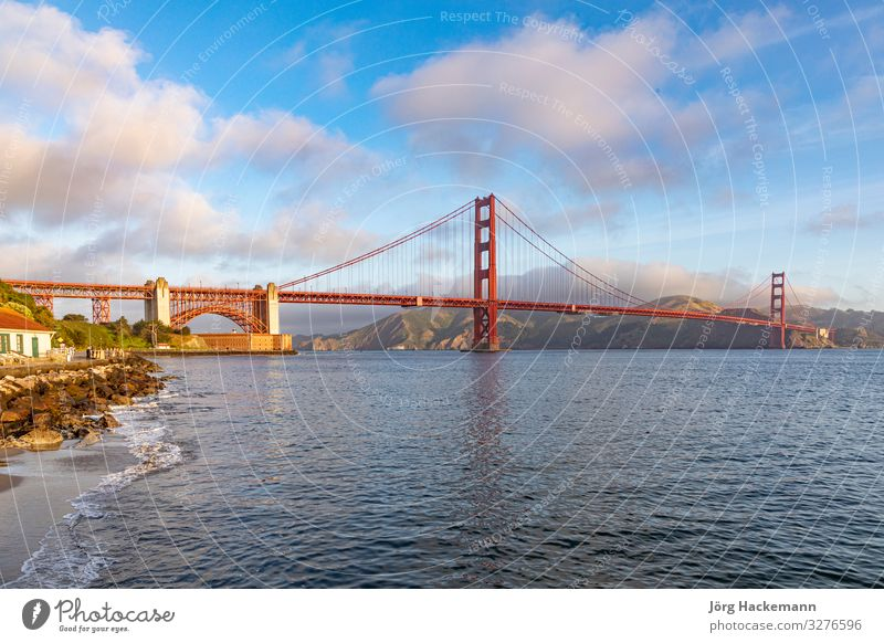 View of Golden Gate Bridge along the coastline in San Francisco Vacation & Travel Tourism Ocean Nature Sky Coast Skyline Monument Metal Historic Blue Red
