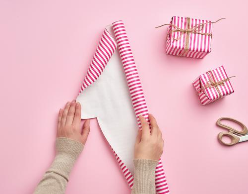 female hands unfold a roll of wrapping paper Design Winter Decoration Feasts & Celebrations Christmas & Advent New Year's Eve Birthday Hand Paper Package