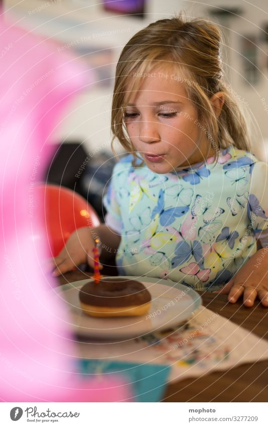 Girl in a dress blows out candle on doughnut First day at school celebration shoulder stand girl School Schoolchild blow out Blow First class first school day