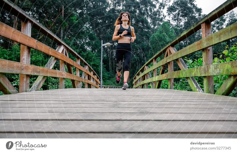 Woman running through an urban park Leisure and hobbies Sports Success Human being Adults Nature Lanes & trails Sneakers Fitness Thin Endurance Effort