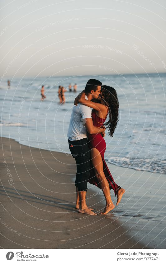 Couple kissing on beach at sunset Summer Beach Ocean Human being 2 18 - 30 years Youth (Young adults) Adults Beautiful weather Dress Long-haired Sand Kissing
