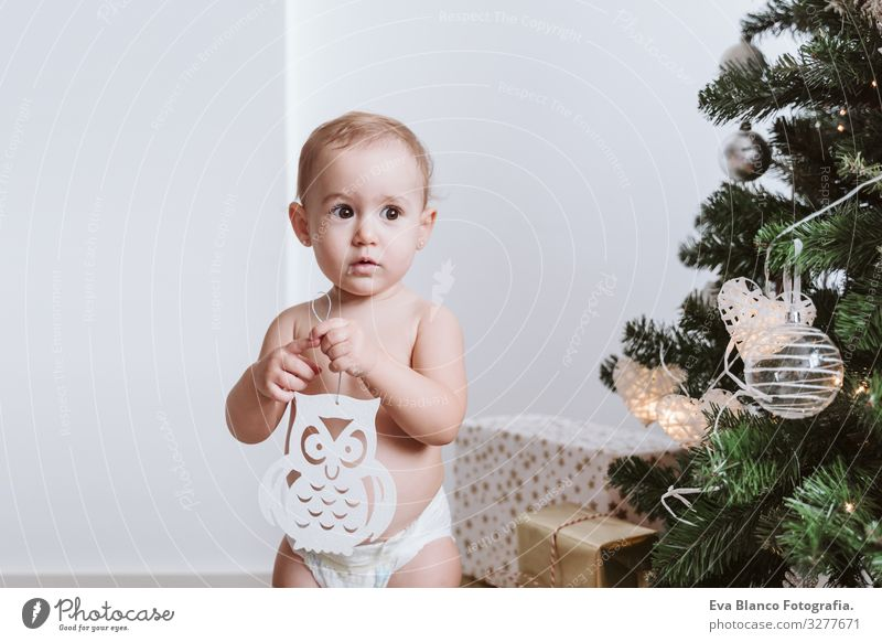 cute baby girl wearing diaper decorating Christmas Tree Nappy Happy Cute Baby Girl one year Christmas & Advent Joy Family & Relations Love Decoration Infancy
