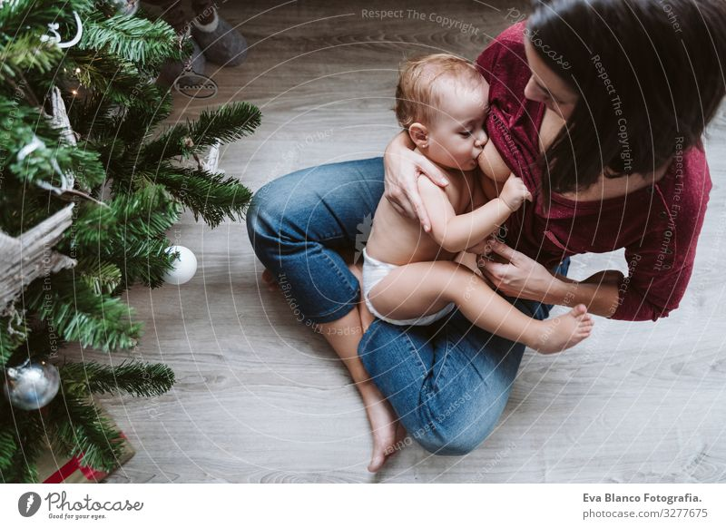 mother breastfeeding her baby girl by the Christmas tree Appease To feed Eating Natural Food Mother motherhood Happy Cute Baby Girl one year decorating