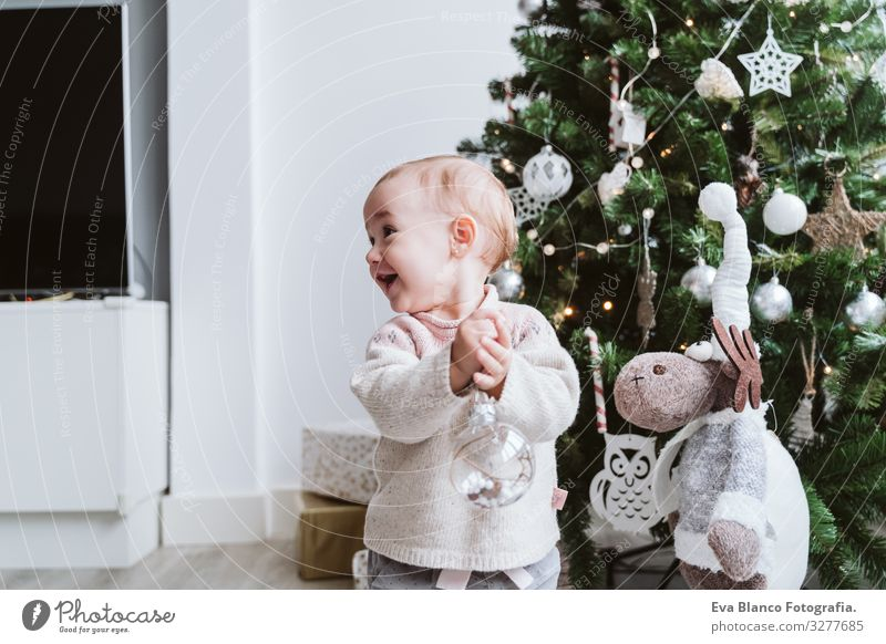 happy baby girl decorating the Christmas tree Happy Cute Baby Girl one year Christmas & Advent Tree Joy Family & Relations Love Decoration Infancy motherhood