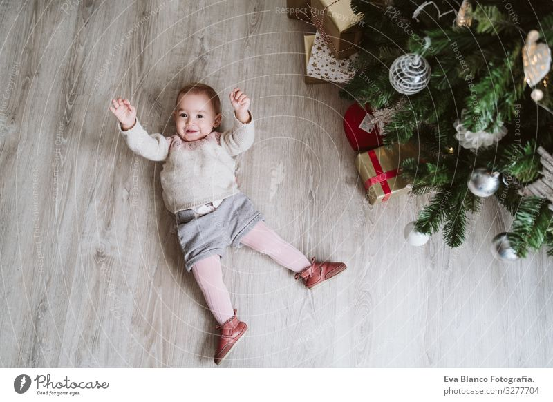 cute baby girl lying on the floor by the Christmas tree Lie (Untruth) Joy Happy Cute Baby Girl one year decorating Christmas & Advent Tree Family & Relations