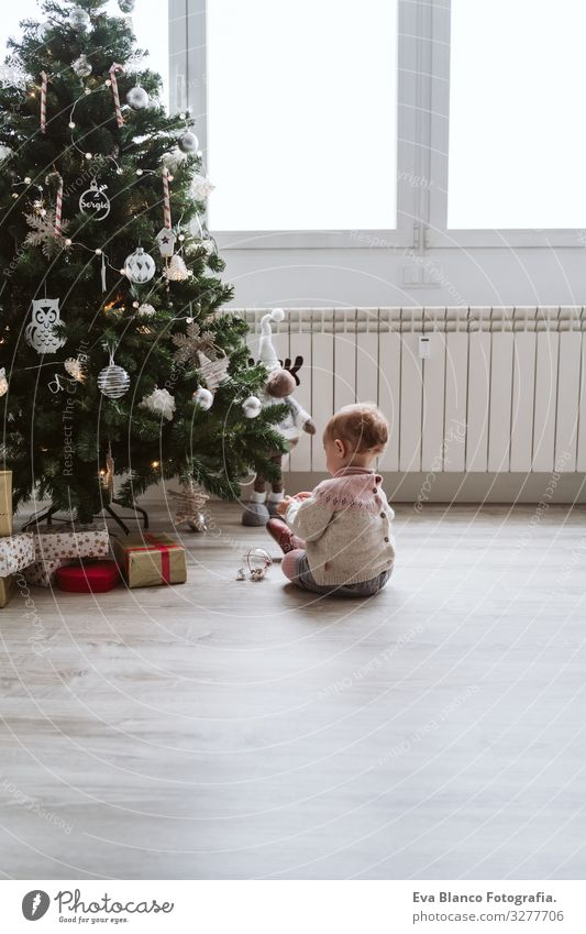cute baby girl decorating the Christmas tree Happy Cute Baby Girl one year Christmas & Advent Tree Joy Family & Relations Love Decoration Infancy motherhood