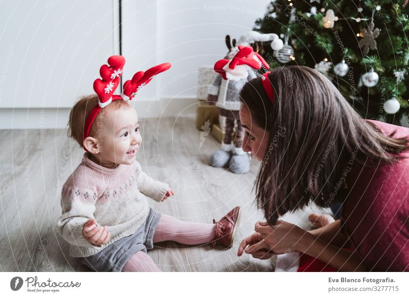 mother and cute baby girl playing at home with reindeer diadem. Christmas concept Playing Santa Claus Mother motherhood Happy Cute Baby Girl one year