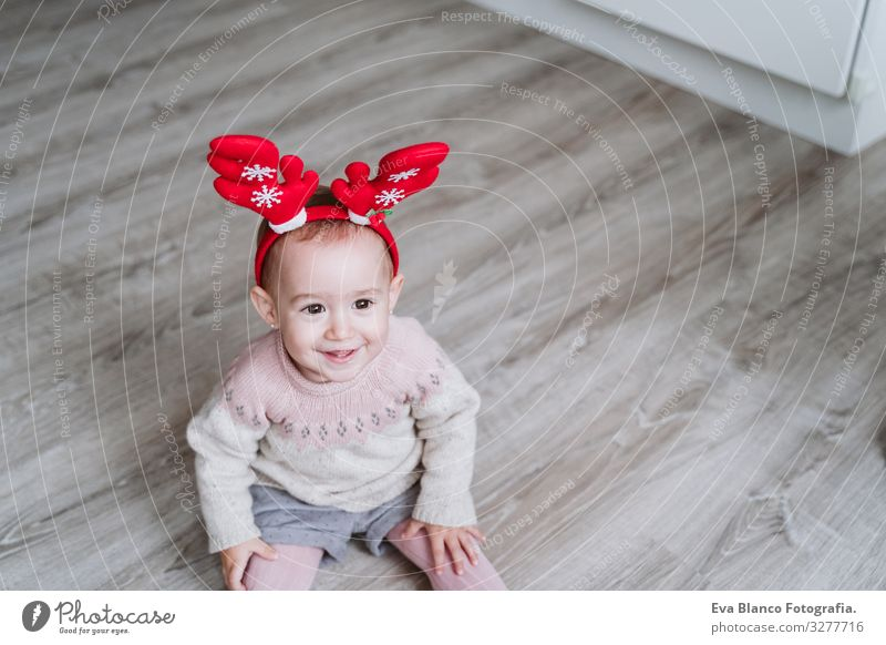 happy baby girl playing at home with reindeer diadem. Christmas concept Playing Santa Claus Mother motherhood Happy Cute Baby Girl one year Christmas & Advent