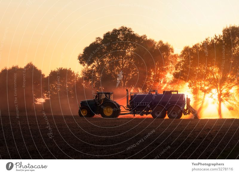 Tractor fertilizing agricultural field at sunset. Agriculture Work and employment Profession Nature Landscape Earth Orange Germany Action agriculture cultivate