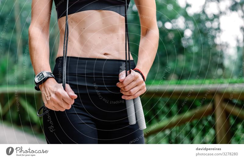Woman posing with skipping rope in a park Body Sports Human being Adults Nature Park Lanes & trails Fitness Thin Pride Defiant Unrecognizable athlete Posture