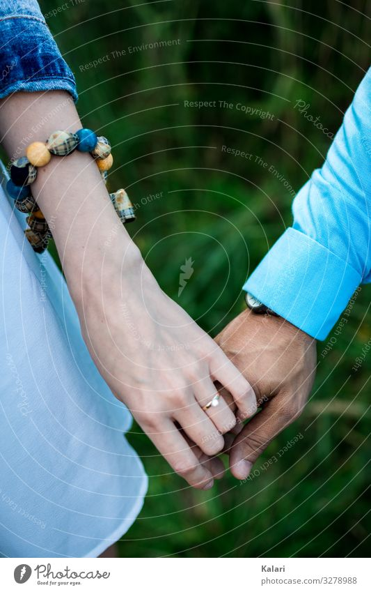 A couple holding hands with engagement ring and blue clothes Couple at the same time Hand stop Wedding People Woman Bride Married couple wedding ceremony Arise