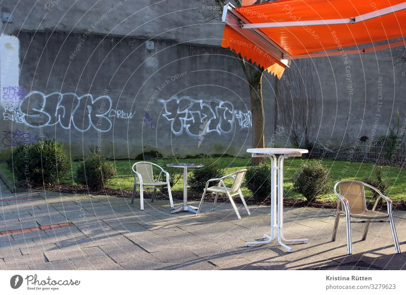 A place in the sun Lifestyle Deserted Wall (barrier) Wall (building) Terrace Graffiti Relaxation Sit Town Orange Table high table Sun blind Weather protection