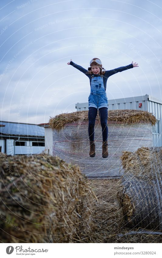 Girl with dungarees and pilot's cap jumps into the straw Joy Leisure and hobbies Playing Adventure Child Infancy 1 Human being 3 - 8 years Clouds Straw