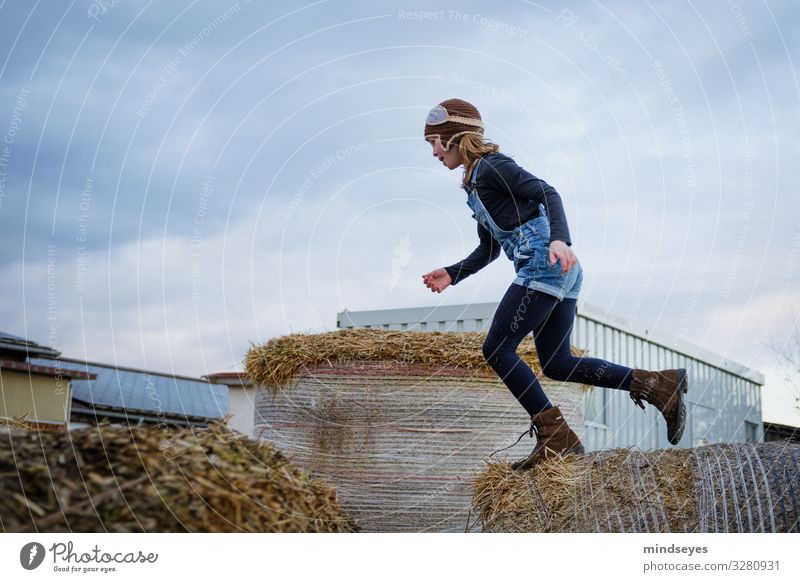 Take a run-up to lift off Playing Adventure Farm Child Girl 1 Human being 3 - 8 years Infancy Nature Straw Bale of straw Cap Jump Athletic Happiness Fresh Happy