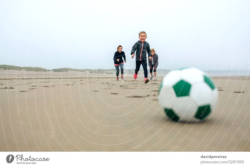 Soccer ball with people running on background Lifestyle Joy Happy Playing Beach Sports Success Child Human being Woman Adults Mother Grandmother