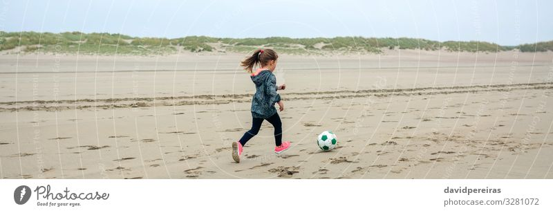 Little girl playing soccer on the beach Lifestyle Joy Playing Beach Sports Child Internet Human being Woman Adults Infancy Nature Plant Sand Autumn Fog Sneakers