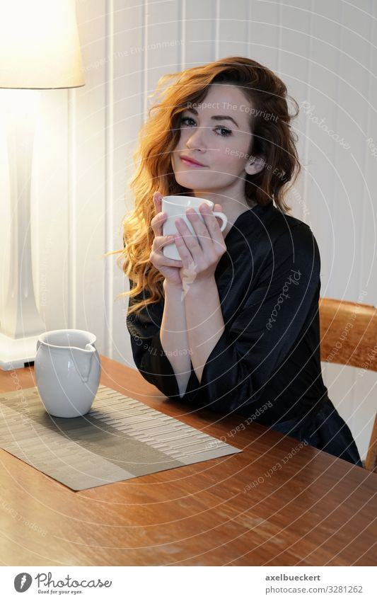 young woman with coffee at the kitchen table Beverage Drinking Hot drink Milk Coffee Tea Cup Mug Lifestyle Beautiful Well-being Contentment Calm