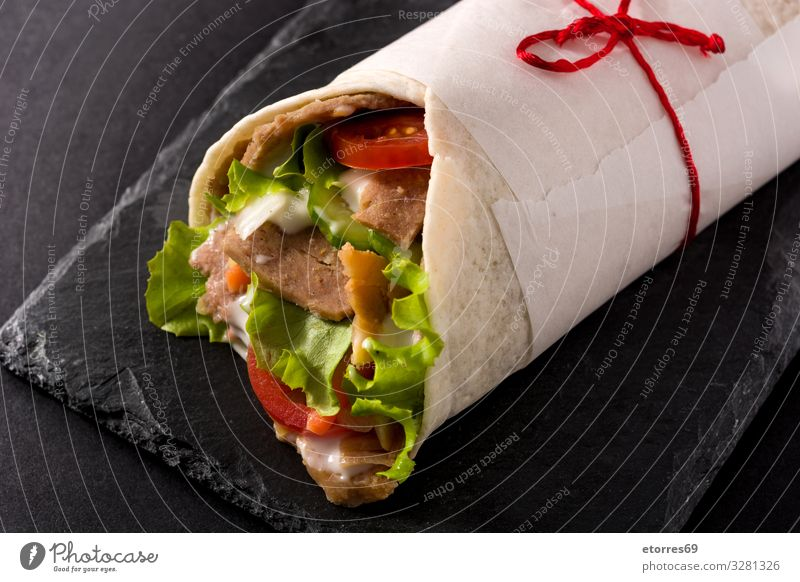 Doner kebab or shawarma sandwich on black slate background doner Kebab Sandwich Wrap Meat Roll Chicken Vegetable Tomato Lettuce Onion Herbs and spices Sauce