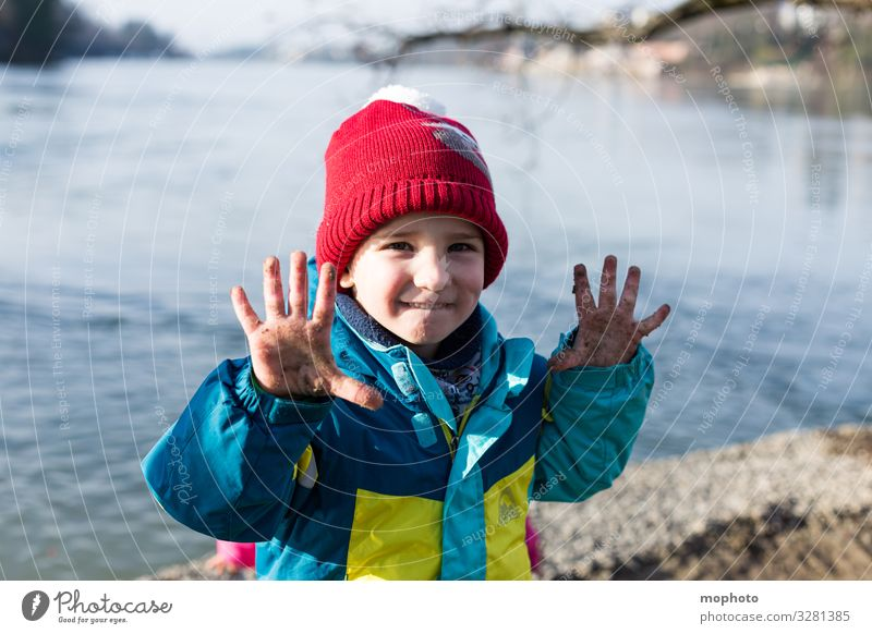 Boy with dirty fingers on water Nature variegated out filth Dirty experience Fingers by hand hands Jacket Boy (child) chill Child cap natural Rhine Red frowzy