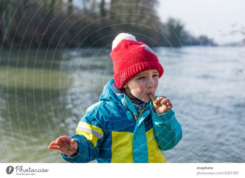 Boy with dirty fingers licks thumb Nature variegated out filth Dirty experience Fingers by hand hands Jacket Boy (child) chill Child Mouth cap natural Rhine Red