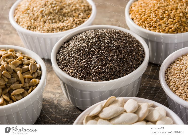Assortment of different seeds in bowl on wooden table Food Healthy Eating Food photograph Seed Seeds Ingredients Grain Exceptional Pumpkin linen chia Sunflower