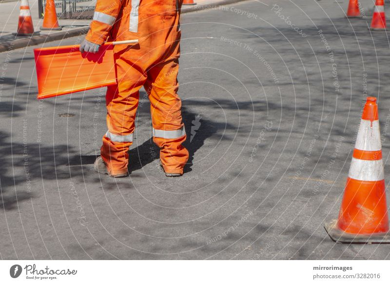orange suited man directing traffic with orange flag on a blacktop road Work and employment Profession Construction site Industry Tool Human being Man Adults