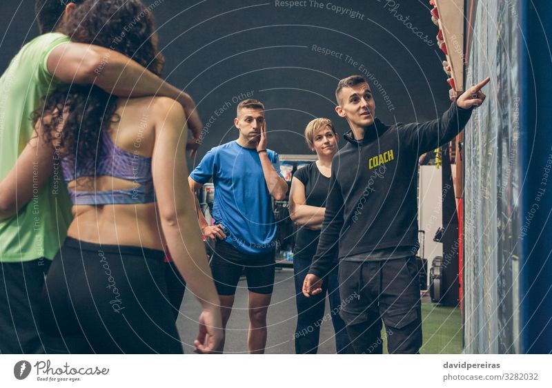 Coach explaining to athletes in the gym Lifestyle Sports Blackboard Human being Woman Adults Man Group Fitness Listening Athletic coach Gymnasium Explain