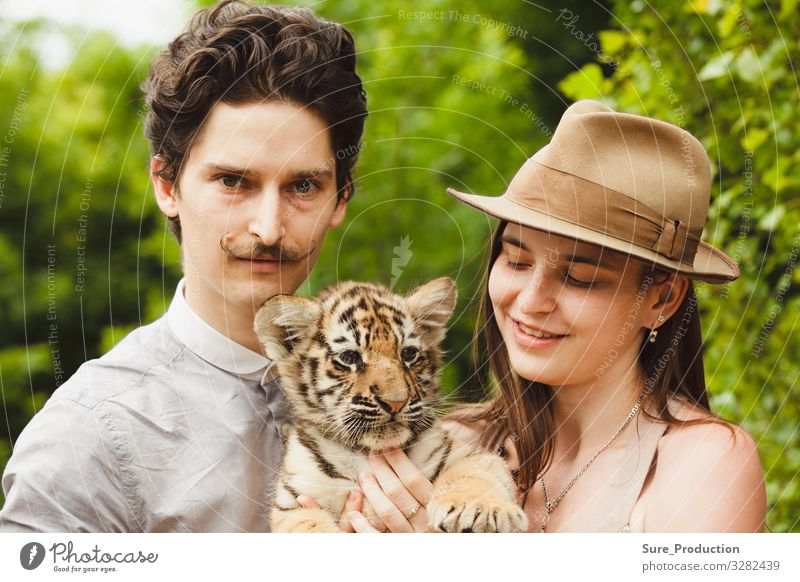 A man and woman hold tiger cub angry animal background bengal black cat close closeup eater face forest friend glamour hat head hunter jungle macho mustche