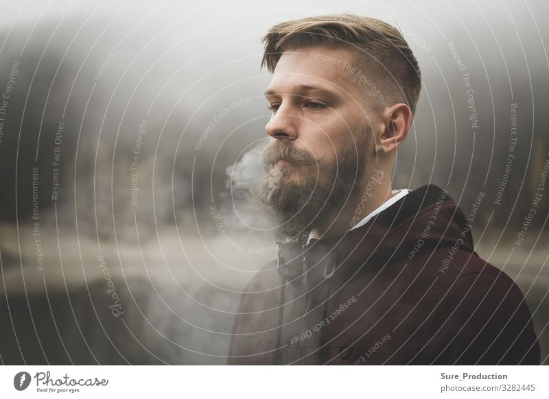 Pretty bearded man smokes cigarette Blows out steam through nostrils Smoke Man more adult Earnest Beard youthful Caucasian Style stylish background Cigarette