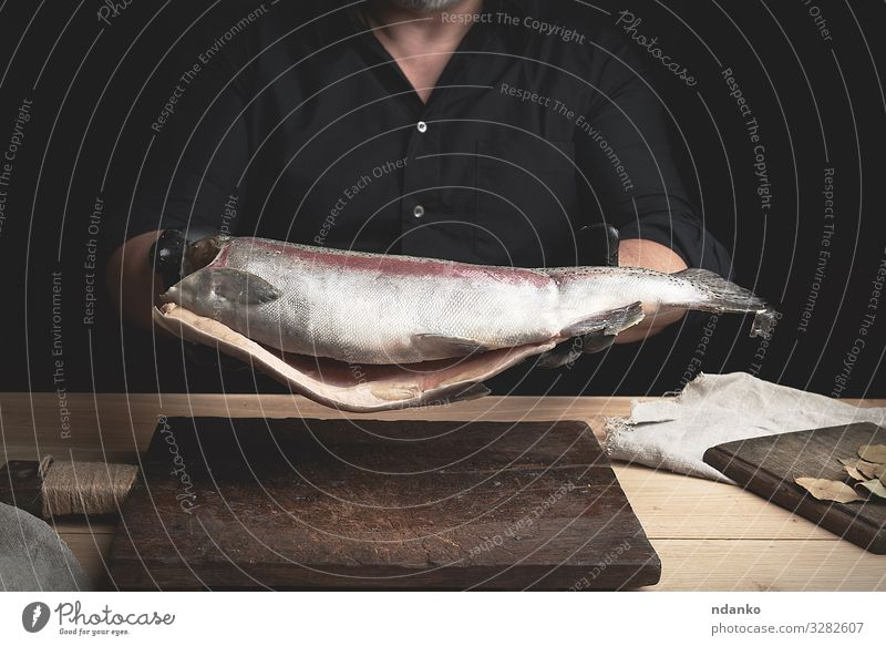 headless salmon fish Meat Fish Seafood Nutrition Dinner Table Kitchen Tool Man Adults Hand Gloves Wood Fresh Large Brown Black board Caucasian chef cook cooking