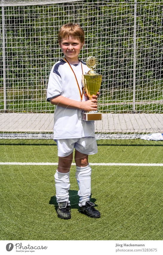 young boy keeps proudly the cup in its hand after the game Joy Happy Playing Club Disco Sports Soccer Child Boy (child) Friendship Infancy Youth (Young adults)